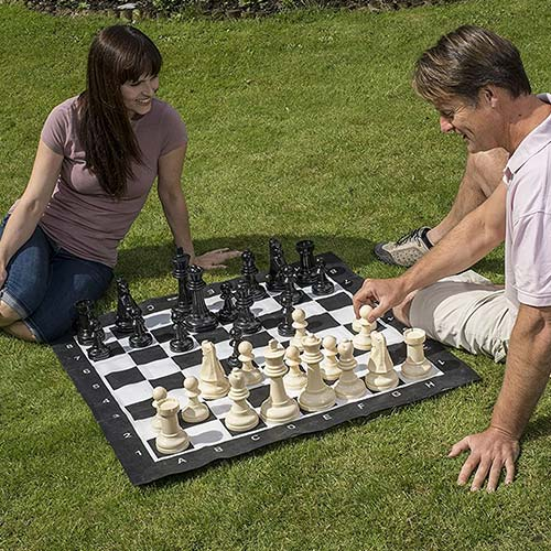 Couple qui joue au échecs sur la pelouse