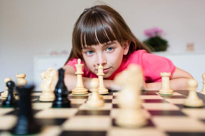 Une enfant qui analyse un échiquier